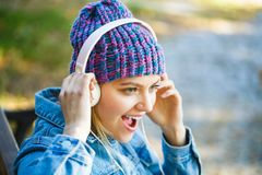 Girl listens to music in headphones. Listening to music.Autumn melody concept. Young woman with big headphones. Cheerful stock image