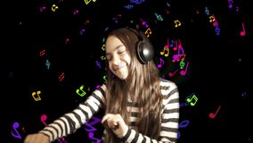 Girl listens to music in headphones. Teenager girl listens to music in headphones and gestures dancing, against a black background. Close up portrait, with a stock video