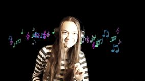 Girl listens to music in headphones. Teenager girl listens to music in headphones and gestures dancing, against a black background. Close up portrait, with a stock video footage
