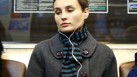 A girl listens to music or watches video on a smartphone in a subway car.  stock video footage