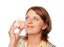 Girl listens to a seashell Stock Image