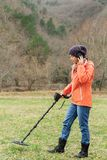 The girl listens to the signal of the metal detector while on the field royalty free stock images