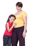The girl listens to a stomach of mother. White background Royalty Free Stock Photography