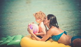 Girl with little boy kid swim on yellow air mattress in the water in the summer.  stock photography