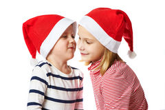Girl and little boy in Santa Claus hat Stock Images