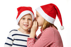 Girl and little boy in Santa Claus hat Stock Image