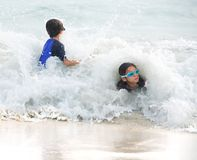 Girl and little brother hit by big wave Stock Photos