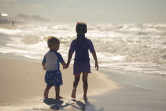 Girl with little brother walking on the beach Royalty Free Stock Images