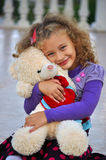 Girl. The little curly-haired girl holding a teddy bear Royalty Free Stock Images