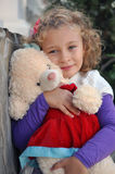 Girl. The little curly-haired girl holding a teddy bear Royalty Free Stock Image