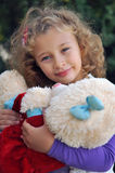 Girl. The little curly-haired girl holding a teddy bear Stock Photo