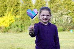 Girl. Little girl giving hand made heart on blurred background Stock Images