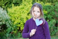 Girl. Little girl holding hand made heart on blurred background Stock Images