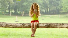 Girl little with long hair is playing on smartphone sitting in a tree on beautiful summer day. Girl little with long blonde hair plays on smartphone sitting in a stock video footage