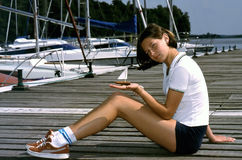 Girl with a little sailing-boat. A girl sitting in a marina with a tiny boat in hand Stock Photography