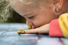 Girl with a little snail Royalty Free Stock Images