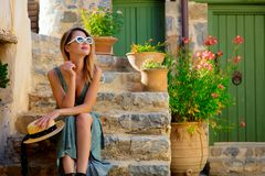 Girl on little village street on Crete, Greece. Young redhead girl in green dress on little village street on Crete, Greece royalty free stock photography