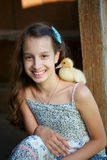Girl with little yellow duckling in summer village Royalty Free Stock Photos