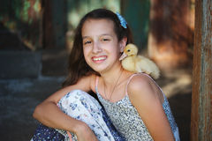 Girl with little yellow duckling in summer village Stock Photo