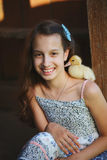 Girl with little yellow duckling in summer village Stock Photos