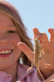 Girl with lizard. Young girl holding a biting lizard in her hand Stock Images