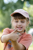 A girl with a lizard in her arms. Dirty little girl caught a lizard on a farm Royalty Free Stock Photography