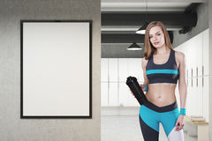 Girl in locker room with framed poster, front. Girl in sportswear in a locker room with framed poster hanging on a light gray wall, a row of white storage Stock Image
