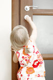 Girl locking door. Back view of a little girl child trying to lock the door Royalty Free Stock Photo