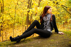Girl on a log. Girl sitting on a log in the autumn forest Royalty Free Stock Photos
