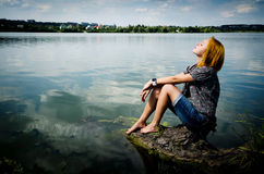 Girl on the log at the lake Royalty Free Stock Photos
