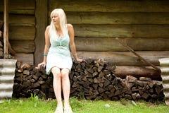 Girl on the log pile Stock Image
