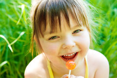 Girl with lollipop. Cute preschool girl with lollipop, in park royalty free stock photography