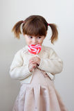 Girl and a lollipop. Beautiful little girl holding a big heart shaped lollipop stock image