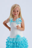 Girl with lollipop. Cute young blond girl with lollipop and turquoise party dress; white studio background royalty free stock photo