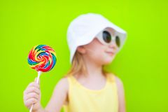 Girl with lollipop. Adorable little girl with lollipop over colorful wall. Focus on candy Royalty Free Stock Image