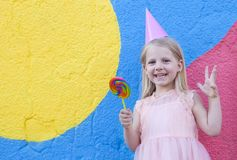 Girl with lollipop. Cheerful little girl with birthday cap on head holding lollipop royalty free stock photography