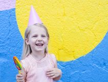 Girl with lollipop. Cheerful little girl with birthday cap on head holding lollipop stock image