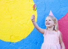 Girl with lollipop. Cheerful little girl with birthday cap on head holding lollipop stock photos
