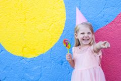 Girl with lollipop. Cheerful little girl with birthday cap on head holding lollipop royalty free stock photo