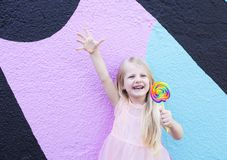 Girl with lollipop. Cheerful little girl with birthday cap on head holding lollipop royalty free stock photos