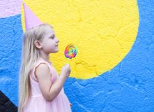 Girl with lollipop. Cheerful little girl with birthday cap on head holding lollipop stock photography