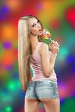 Girl with lollipop. a colorful background Stock Photography