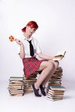 Girl with lollipop sitting on a pile of books Stock Images