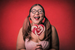 Girl with a lollypop. Girl wearing glasses and pig tail holding a lollypop Stock Image