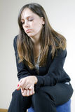 Girl lonely and sad. Young, beautiful woman, sitting in an empty room, thinking, looking a little bit sad and lonely Royalty Free Stock Photos