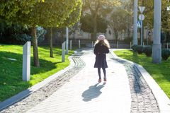 Girl with long blond curly hair in dark blue coat and french beret. Runs along the path of the autumn city, picture from the back Stock Photo