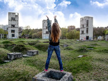 A girl with long blond hair appeals to the sky. She stands on a vacant lot in front of three shattered towers and raised her arms upwards Royalty Free Stock Photos