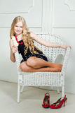 Girl with long blond hair on armchair. Portrait beautiful girl with long blond hair on armchair Stock Photos