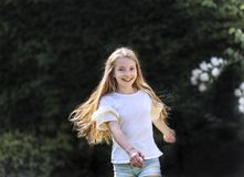 Girl with long blond hair dances in the garden on a beautiful spring day and is cheerful stock photo