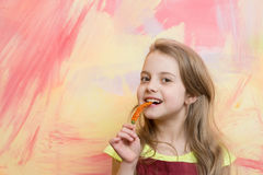 Girl with long blond hair eating red chilly pepper Royalty Free Stock Photos